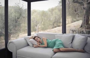 A woman laying comfortably on a couch in front of energy efficient windows.